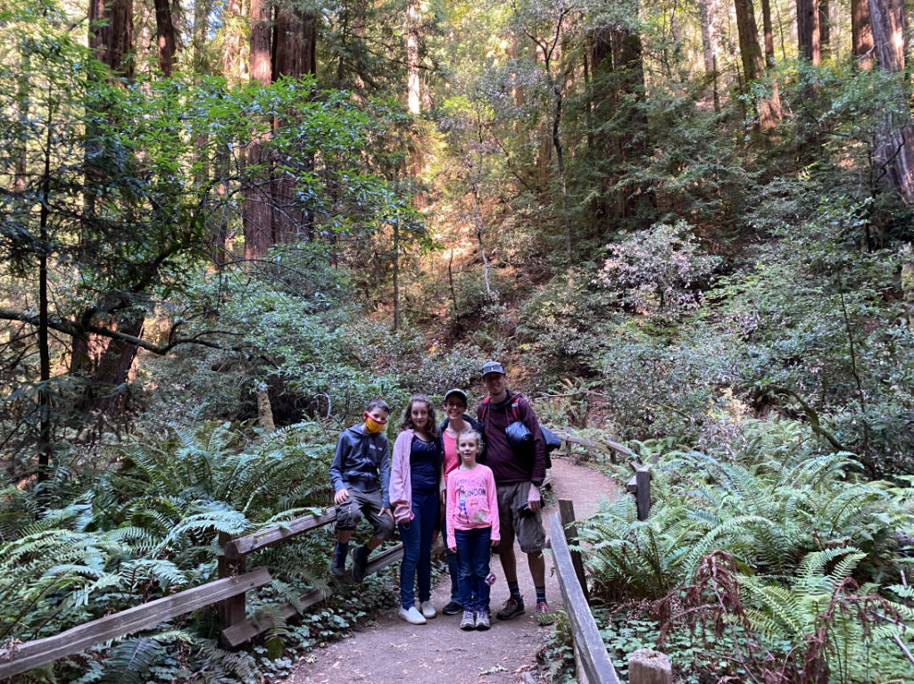 Family posing in Muir Woods on a day tour with Spark Experiences