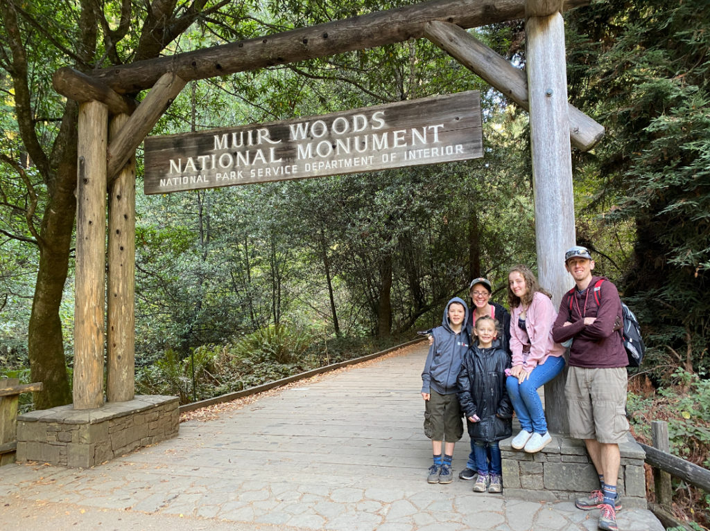 Family posing at the entry to Muir Woods National Monument near San Francisco on a day tour with Spark Experiences